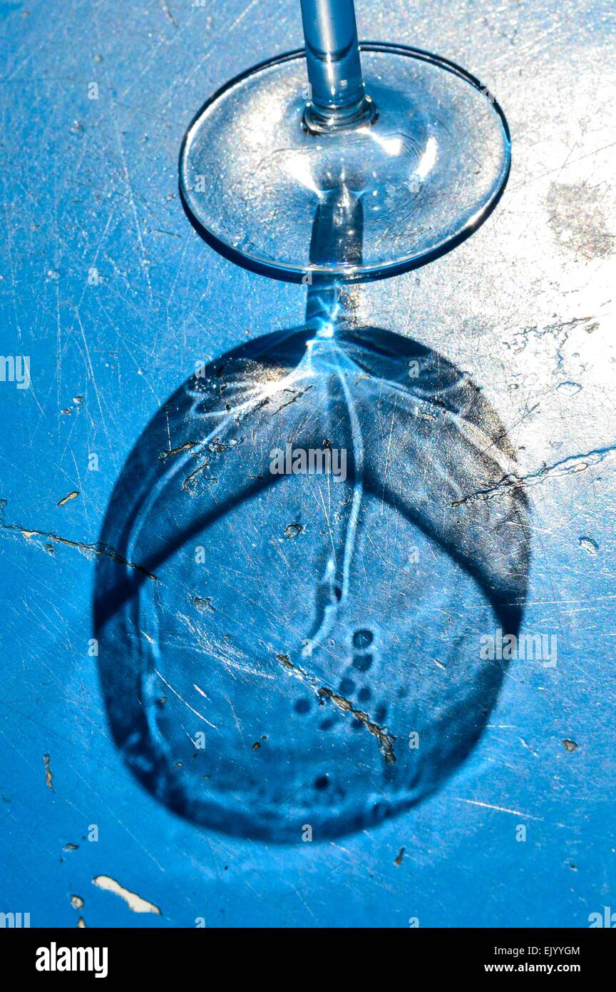 reflections of a wineglas on a blue table - Stock Image