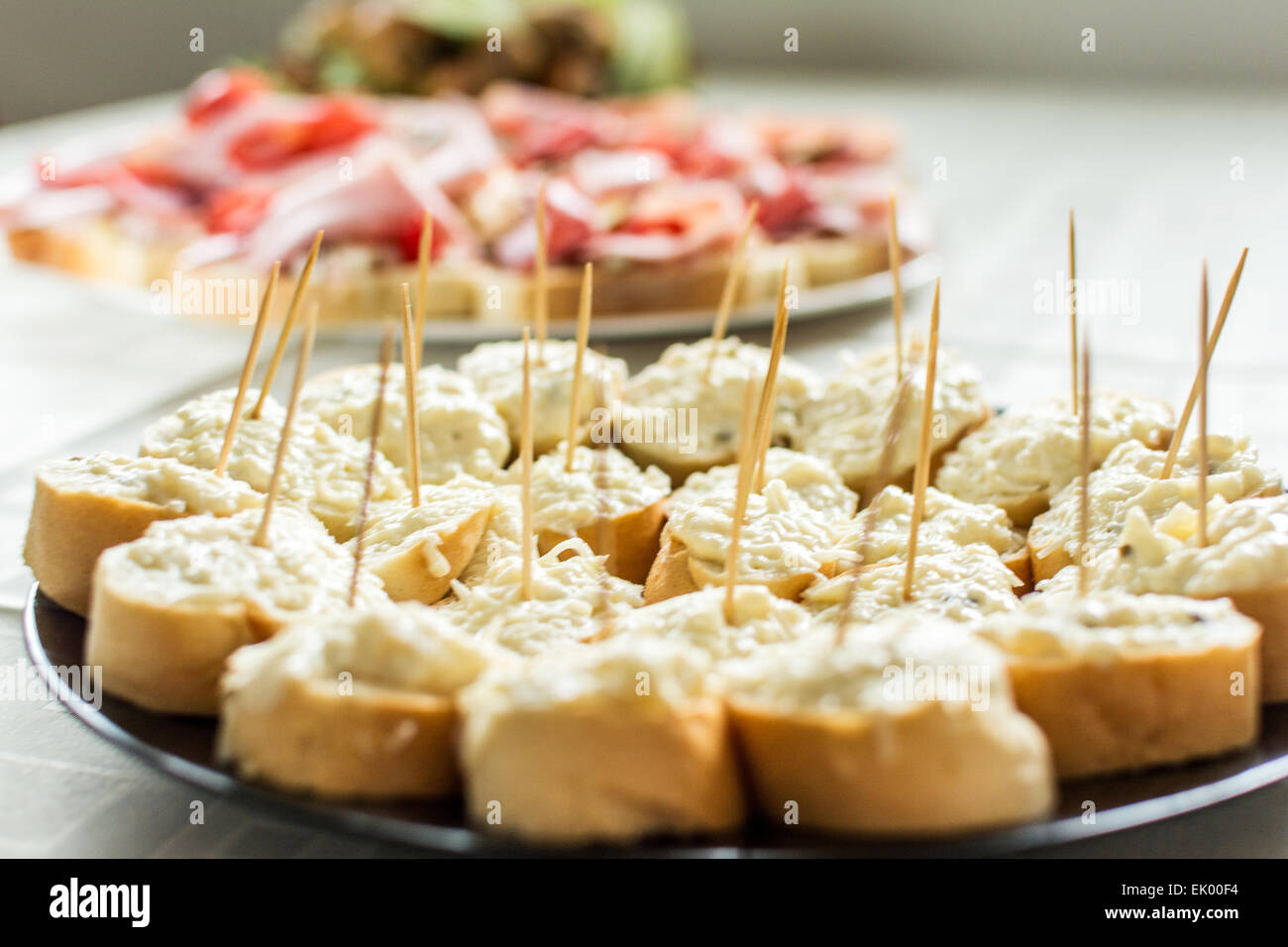 Canapes of garlic and cheese on black plate - Stock Image