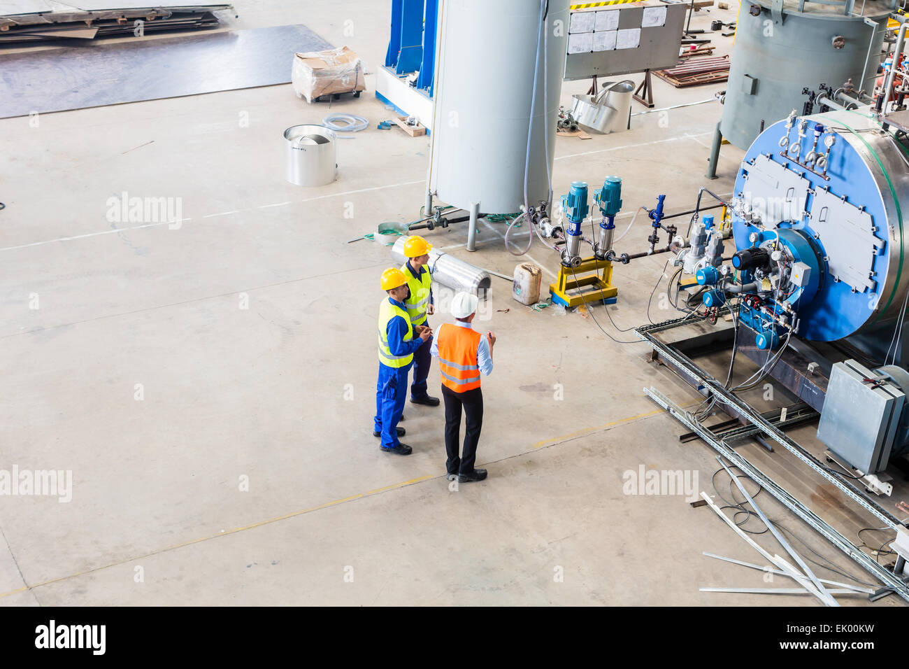 Industrial team of Worker and engineer discussing at machine in factory - Stock Image