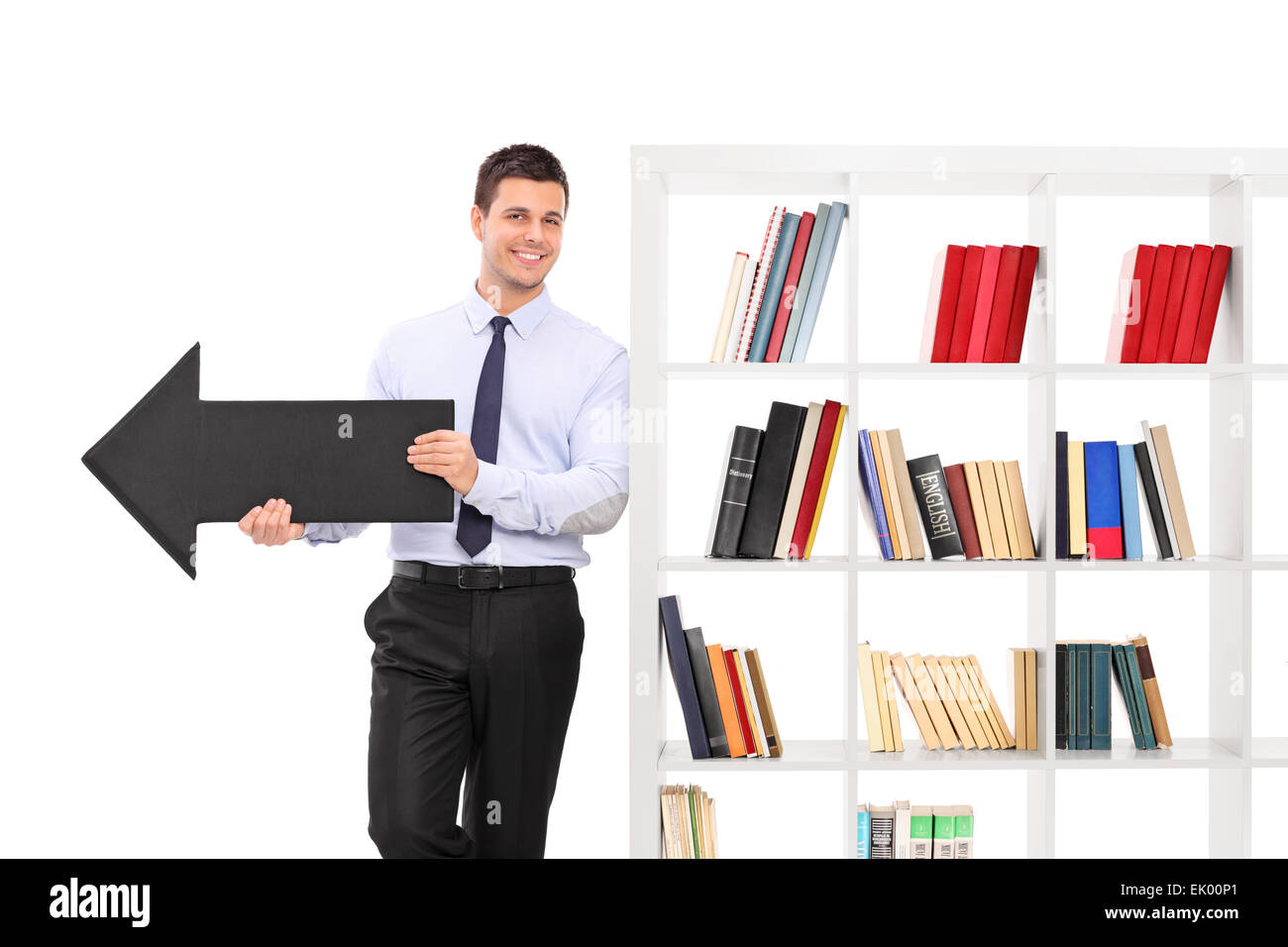 Cheerful Young Guy Holding A Big Black Arrow Pointing Right And Leaning On White Bookshelf Isolated Background