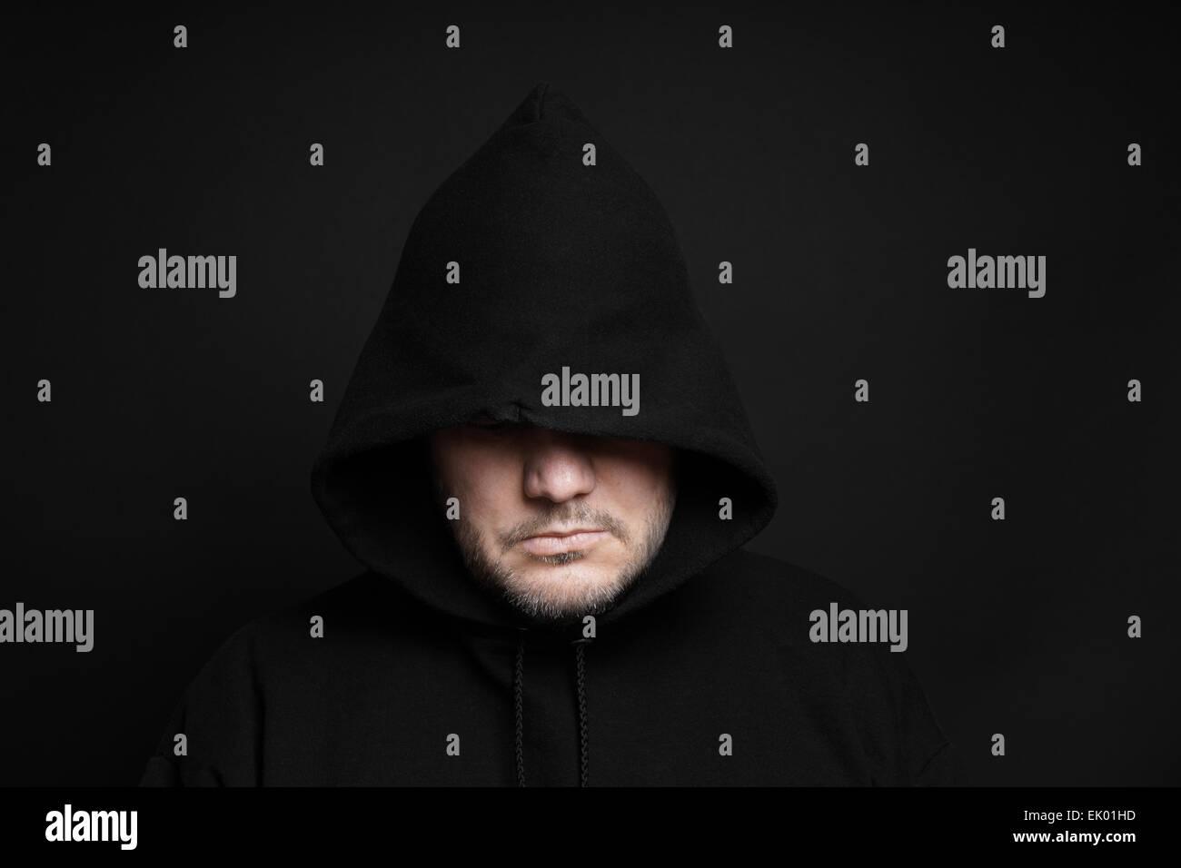man wearing black hoodie hiding eyes - Stock Image