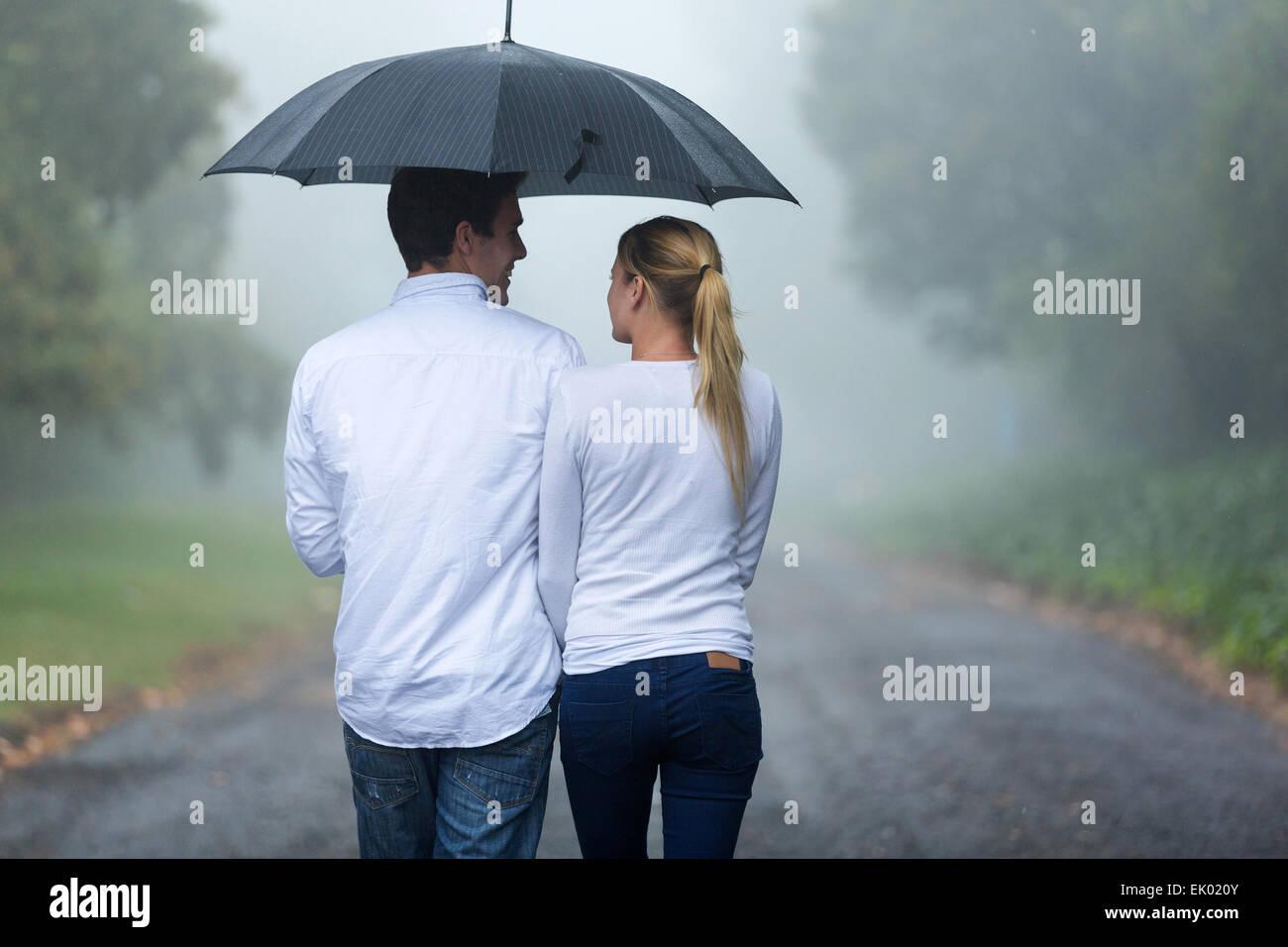 rear view of romantic couple walking in rain - Stock Image