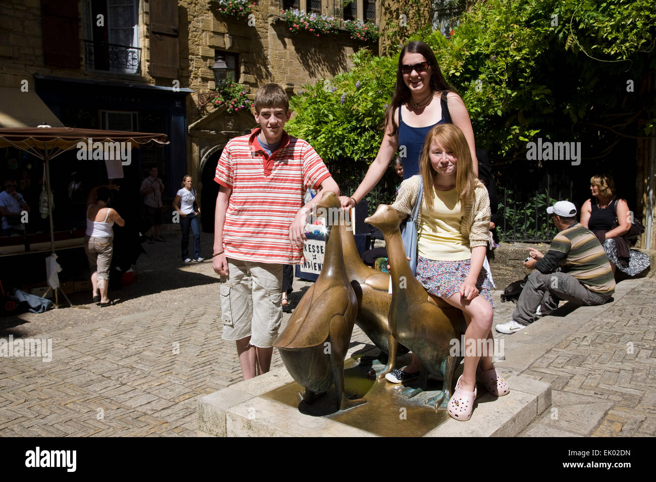 Three teenaged children stand and sit on bronze geese sculptures in Sarlat. - Stock Image