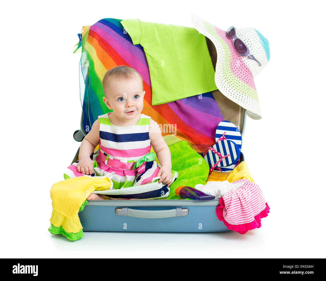 Baby girl sitting in suitcase with things for vacation travel Stock Photo