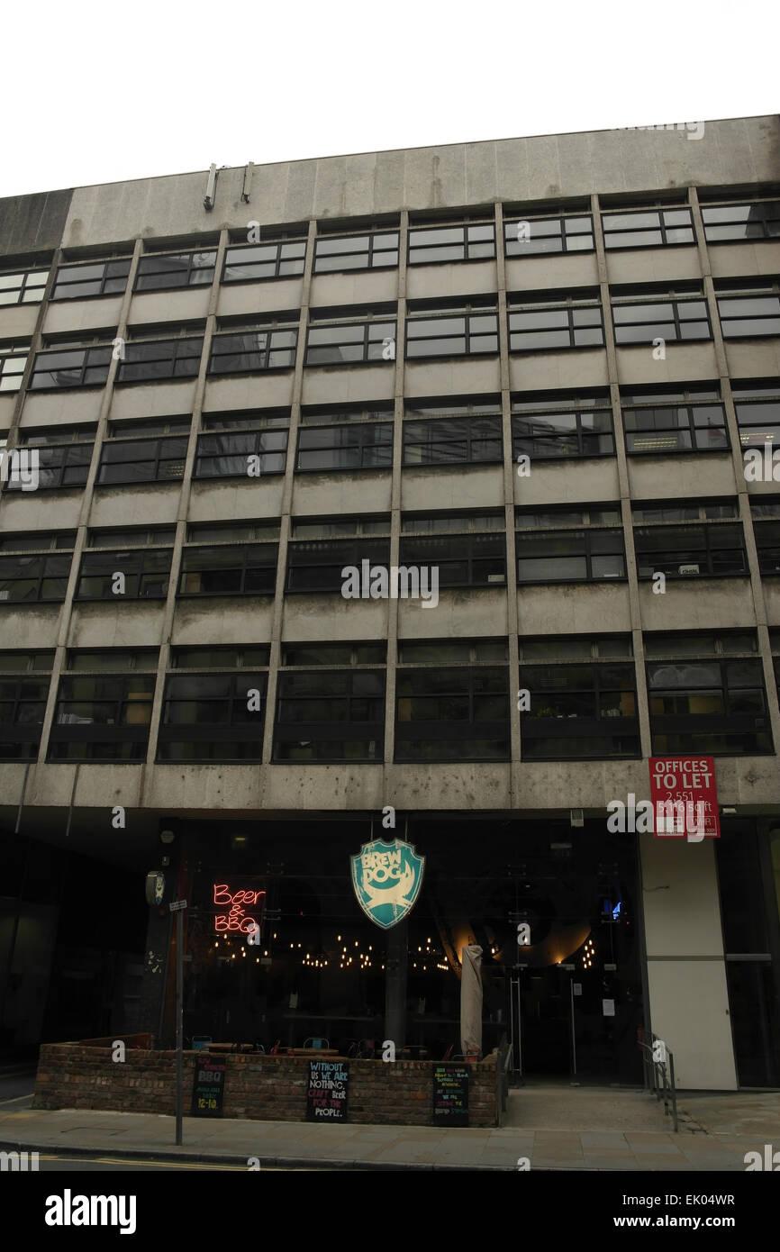 Grey sky portrait electric lights 'Brew Dog' bar, ground-floor 1960s, 8-storey office block, Peter Street, - Stock Image