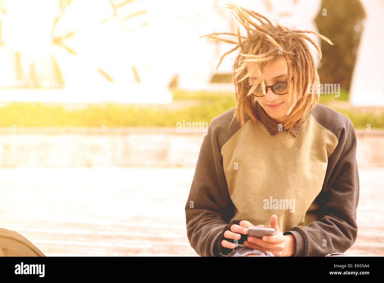 Lifestyle portrait of a young man using a smart phone outdoors warm tones filter applied - Stock Image