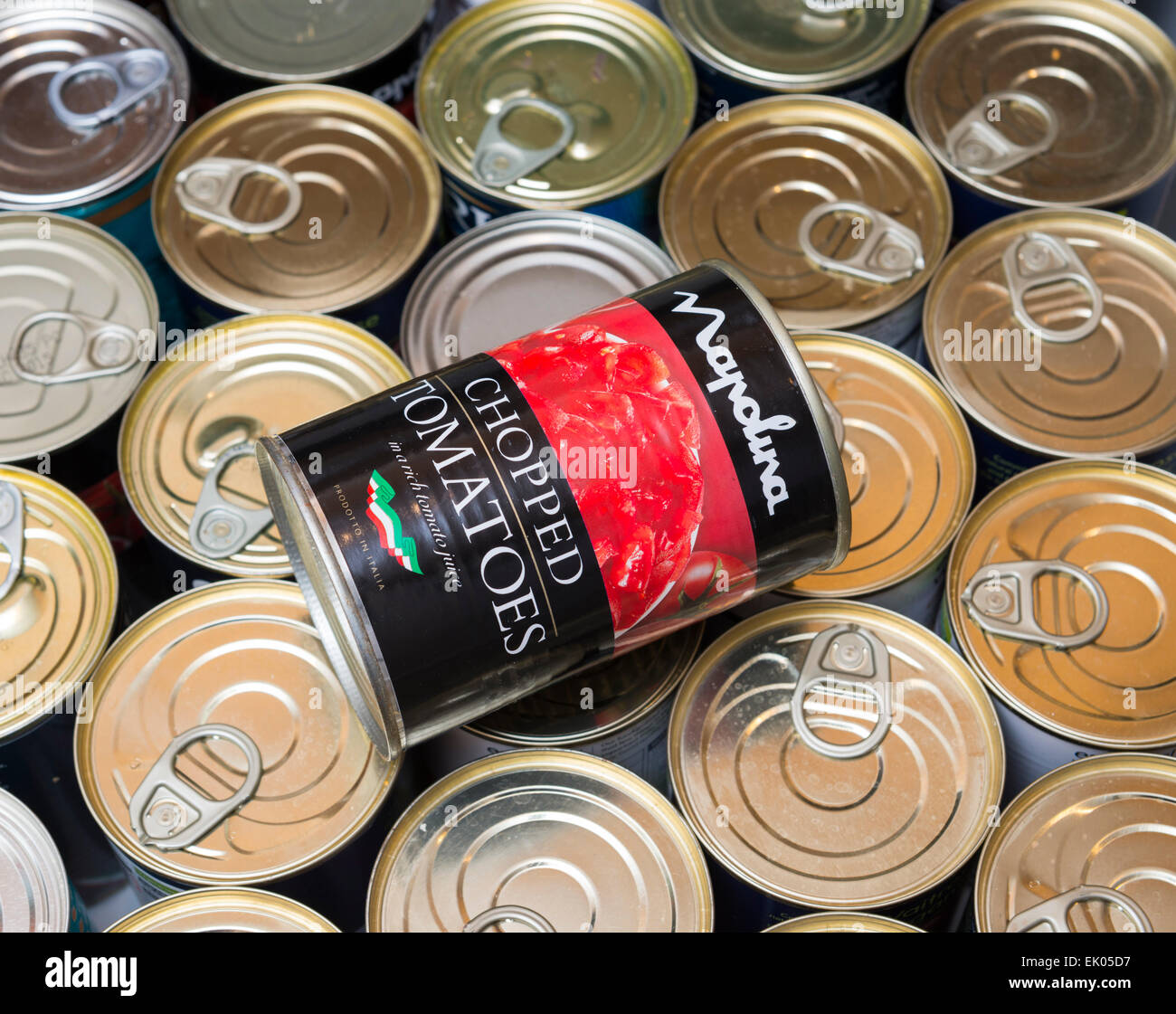 A can of chopped tomatoes in a draw of canned food. - Stock Image