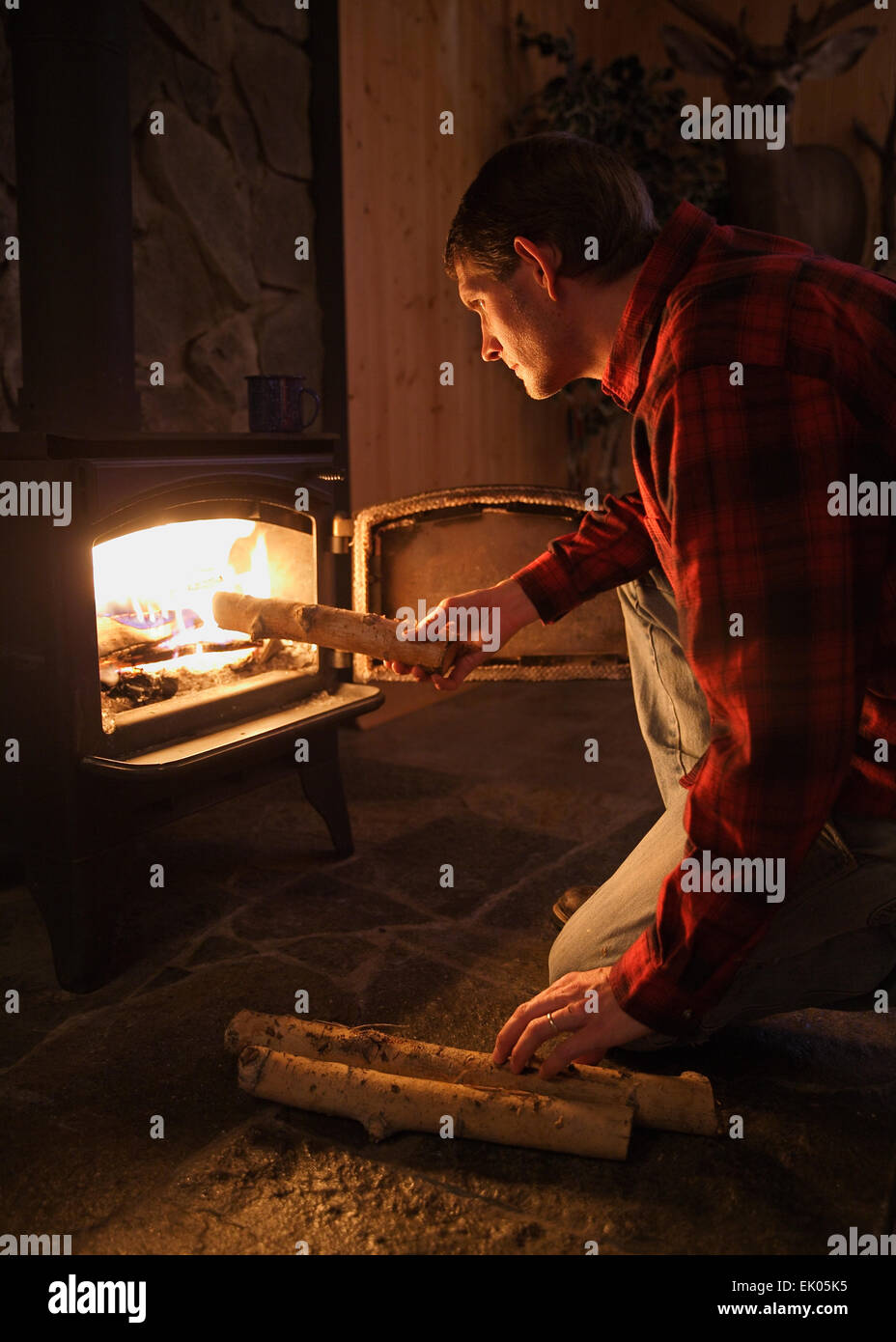 mid-adult man adding logs to a wood burning stove fire in rustic setting - Stock Image