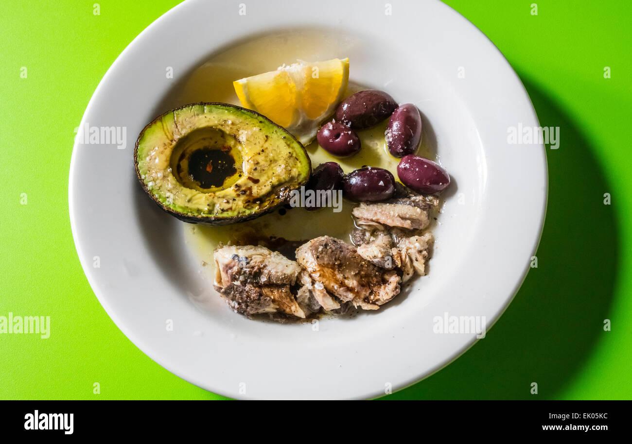 A savory snack of avocado vinagarette Kalamata olives and sardines with a lemon wedge - Stock Image