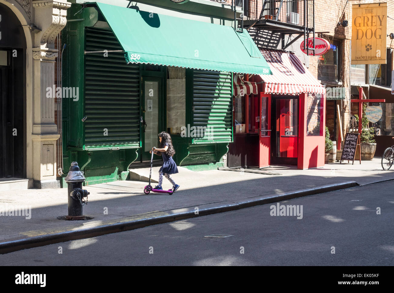A young girl on a kick or push scooter on Mulberry Street in Nolita in New York City - Stock Image