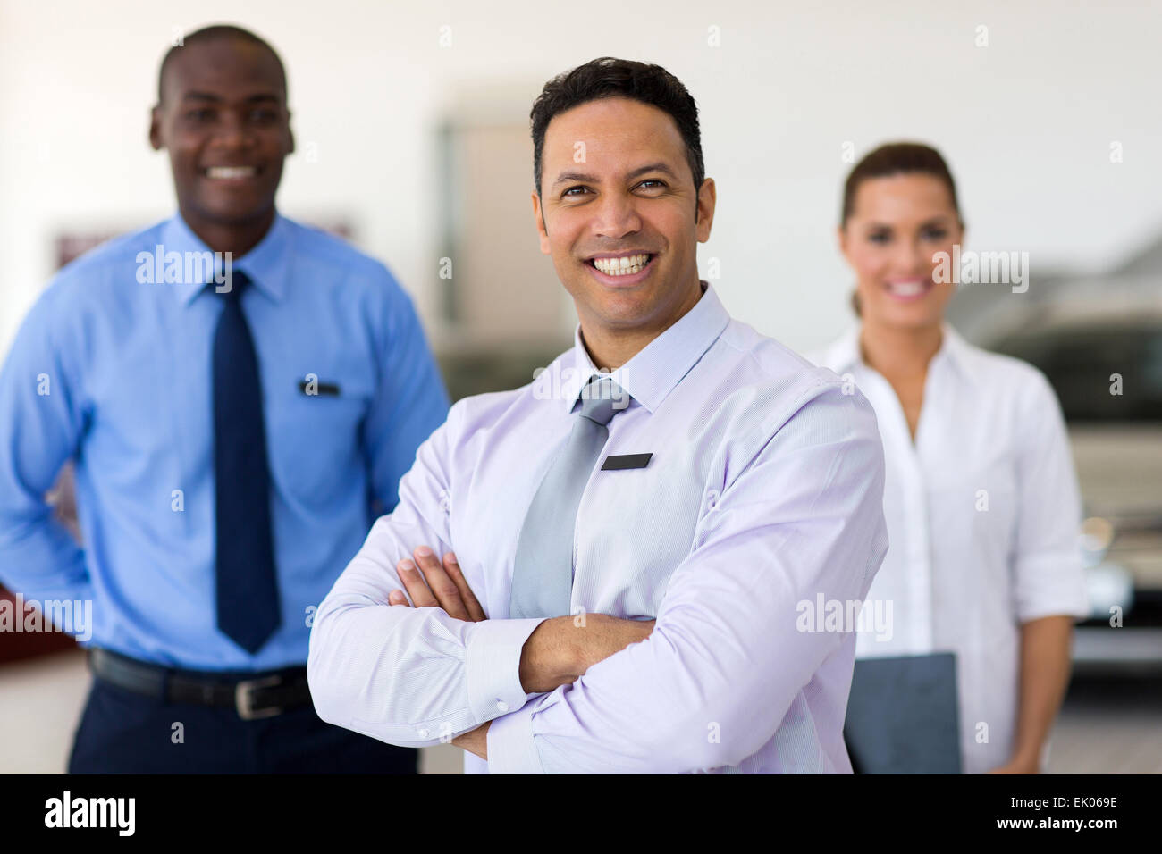handsome middle aged car salesman with colleagues - Stock Image