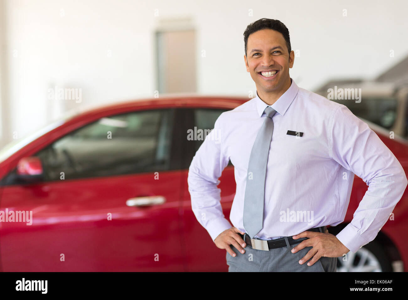 middle aged vehicle sales consultant inside showroom - Stock Image
