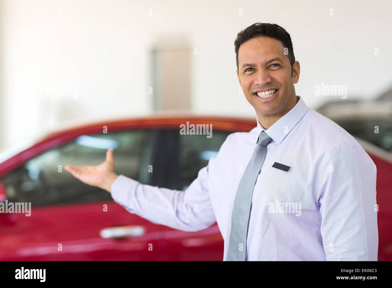 portrait of middle aged salesman presenting new car to clients - Stock Image