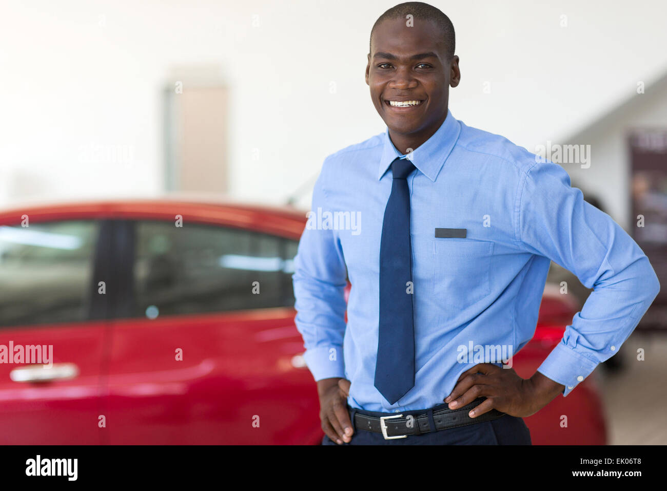 African American vehicle sales consultant inside showroom - Stock Image