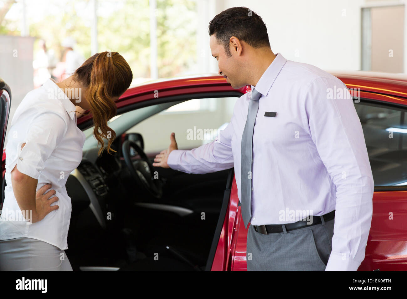 vehicle salesman showing a new car to a potential buyer in showroom - Stock Image