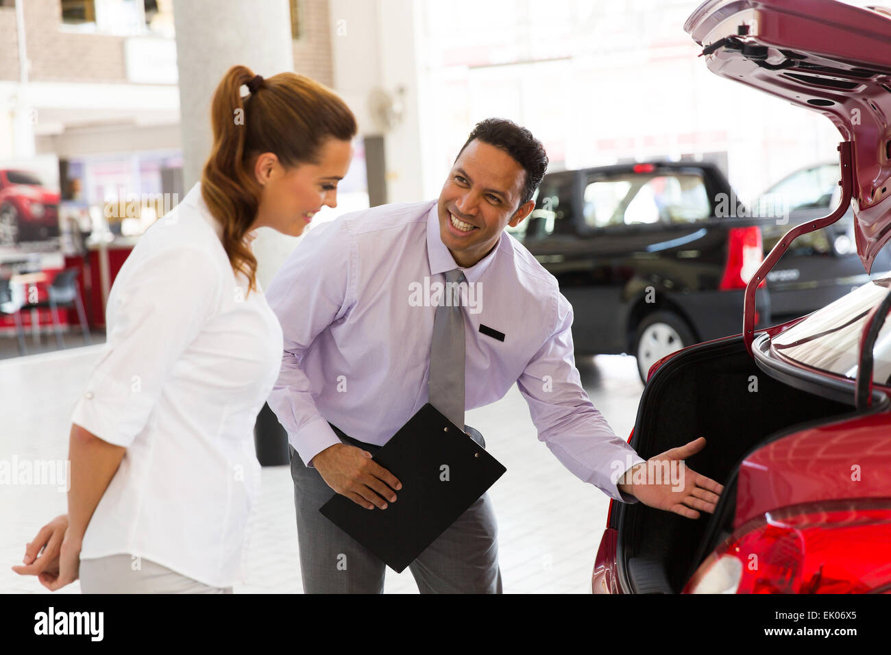 handsome car salesman showing new vehicle to customer - Stock Image