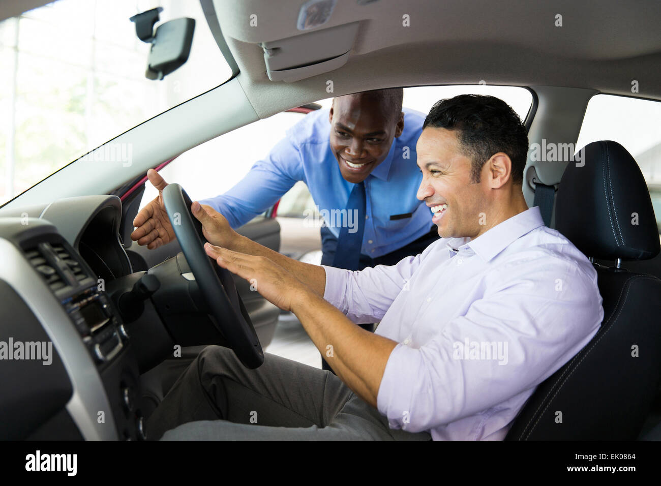 friendly African salesman explaining car features to customer - Stock Image