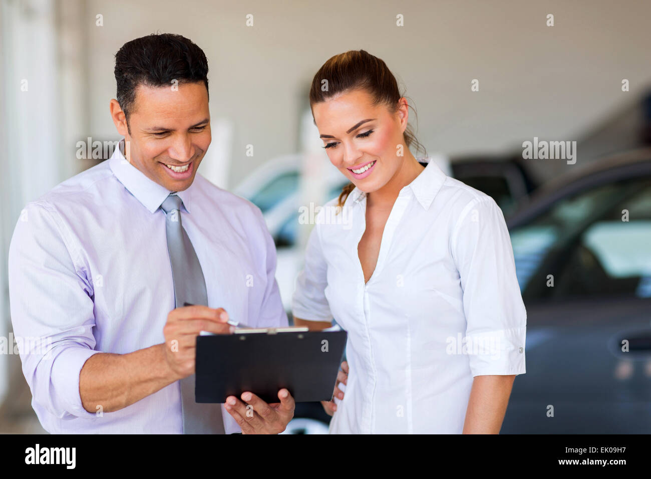 handsome vehicle dealership principal and saleswoman looking at clipboard - Stock Image