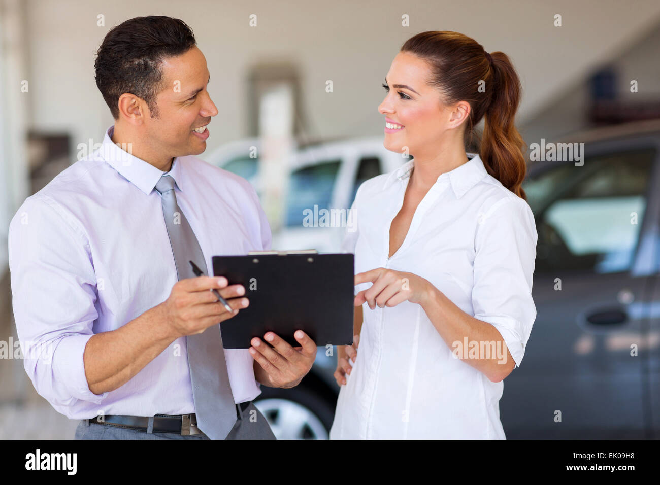 two happy car sales consultants working inside vehicle showroom - Stock Image