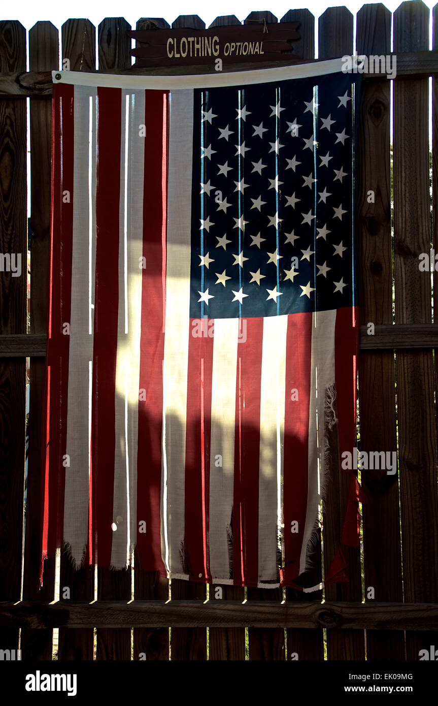 An old tattered and worn american flag is hanging on a stockade fence, backlit by morning sun with clothing optional - Stock Image