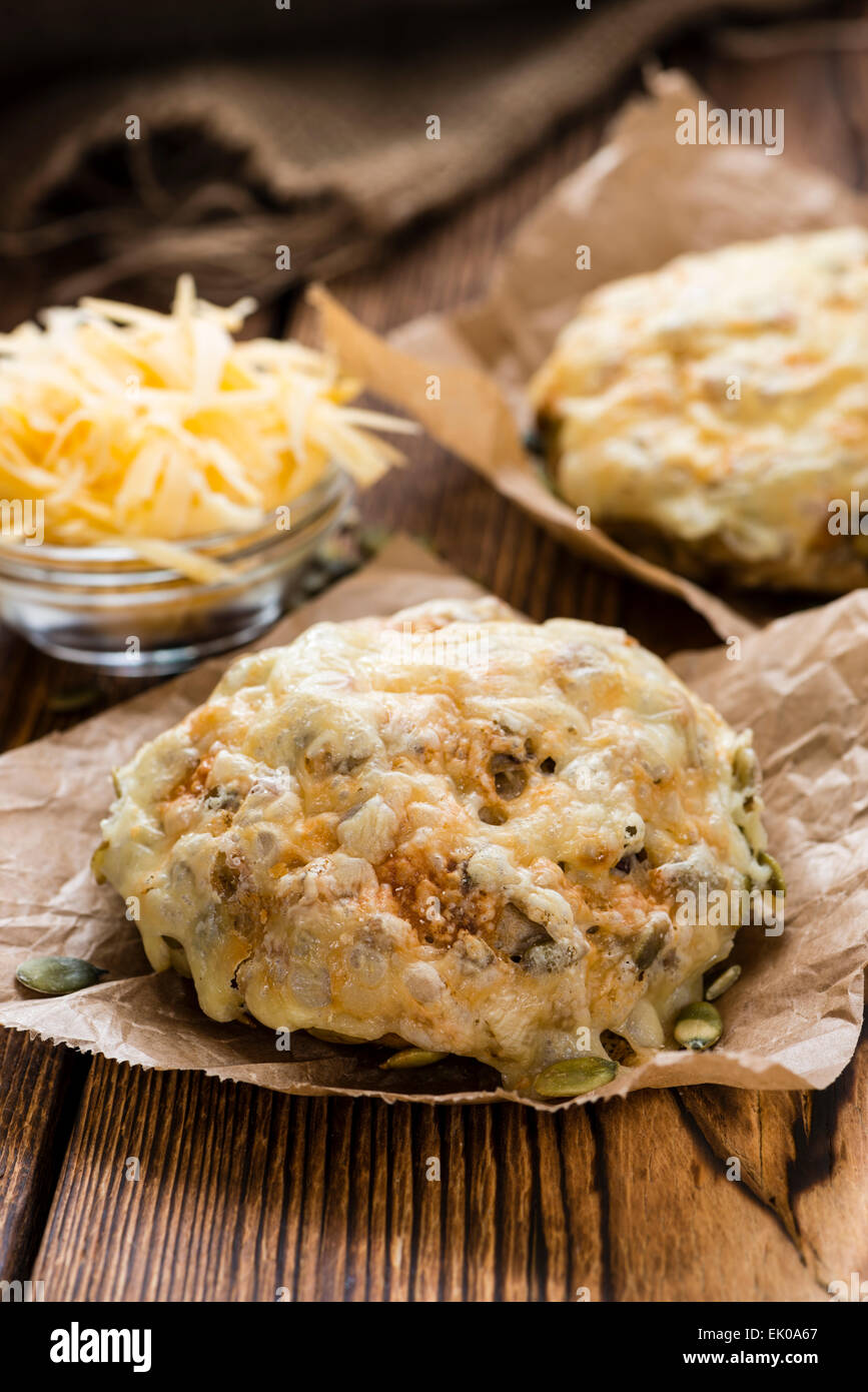 Bun gratinated with Cheese on rustic wooden background - Stock Image