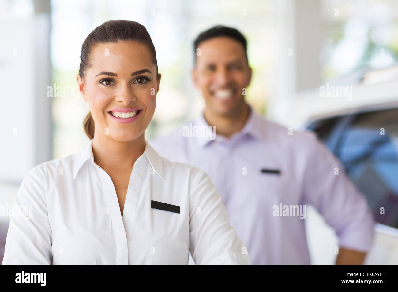 attractive young car saleswoman in showroom - Stock Image