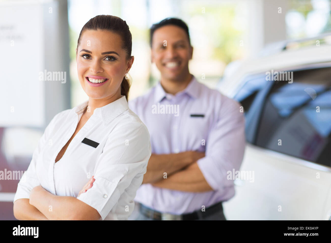 pretty young saleswoman with co-worker on background - Stock Image