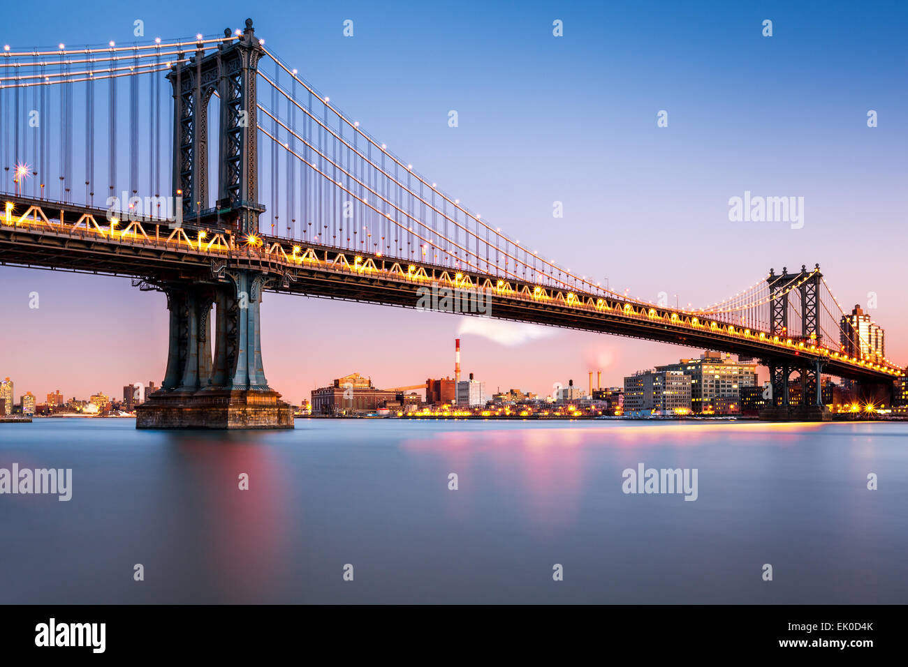 Manhattan Bridge illuminated at dusk (very long exposure for a perfectly smooth water) - Stock Image