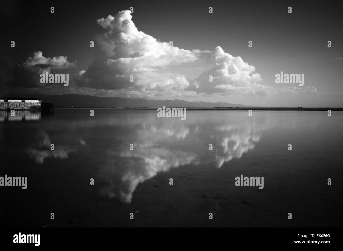Black and white landscape in the coast with clouds and reflection as background - Stock Image