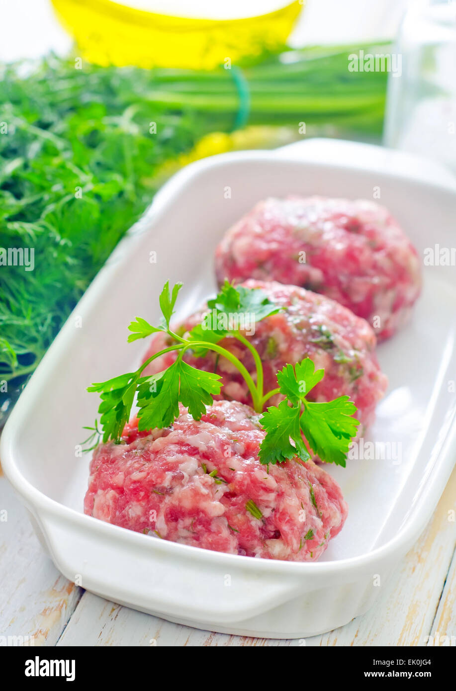 Raw meat balls in the white bowl - Stock Image