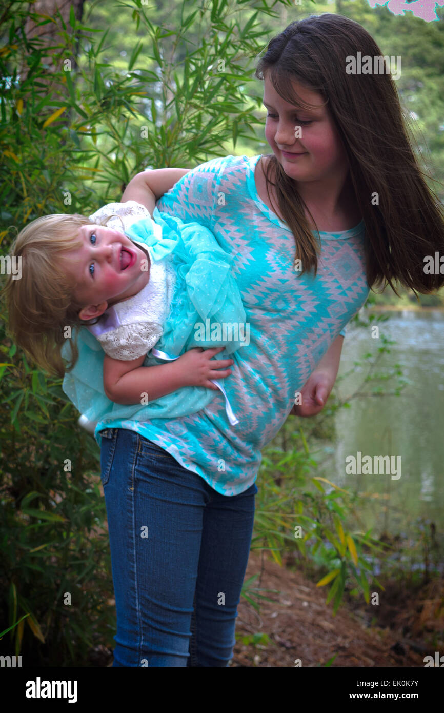 A pre-teen girl plays with her baby sister by a lake at a city park - Stock Image