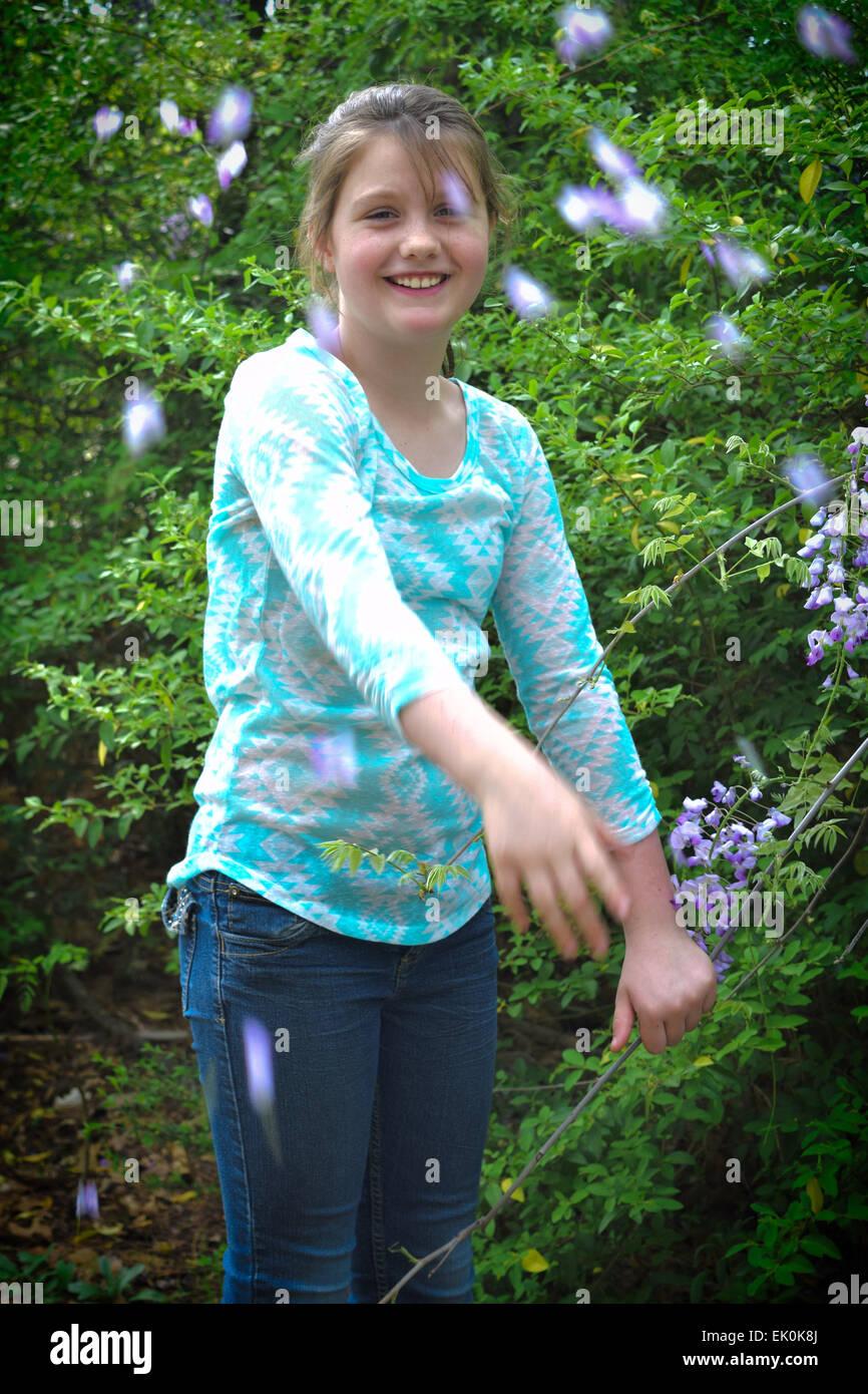 A pre-teen throws petals during a springtime photo shoot at a city park - Stock Image