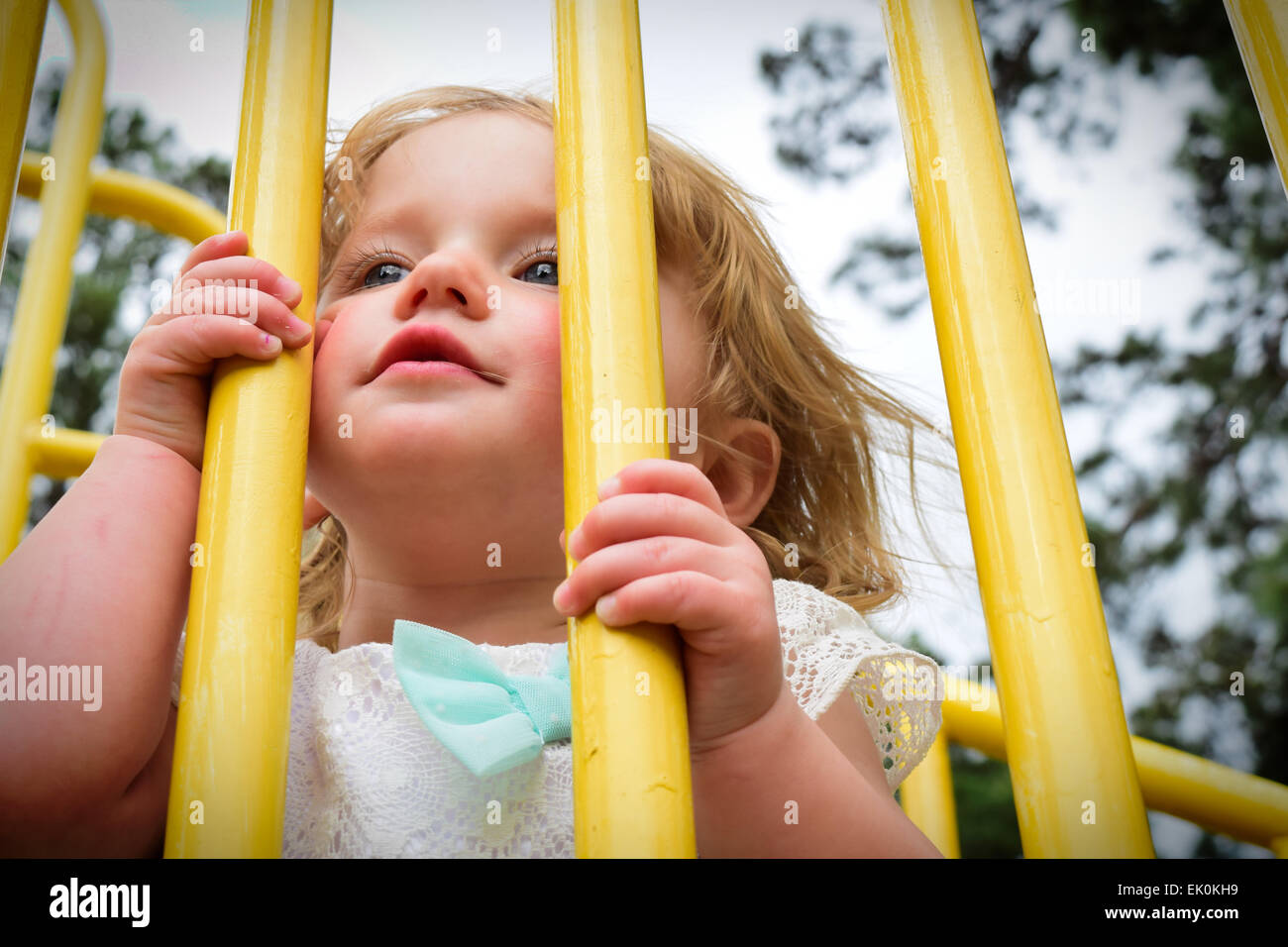 A small, blond toddler peeking through the bars of a jungle gym at a park playground. - Stock Image