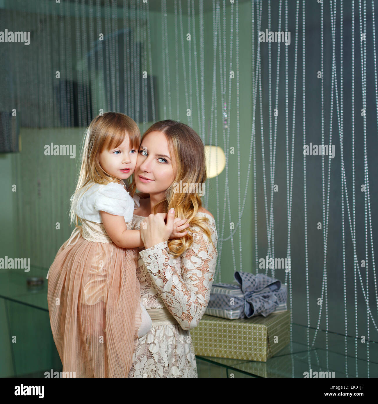 Young mother hugging her daughter tenderly. The concept of family happiness. - Stock Image