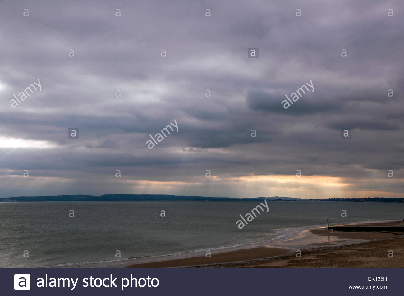 Bournemouth, Dorset, England. 4th April 2015. UK weather. Rays of sunshine break through the clouds over the Purbecs, - Stock Image