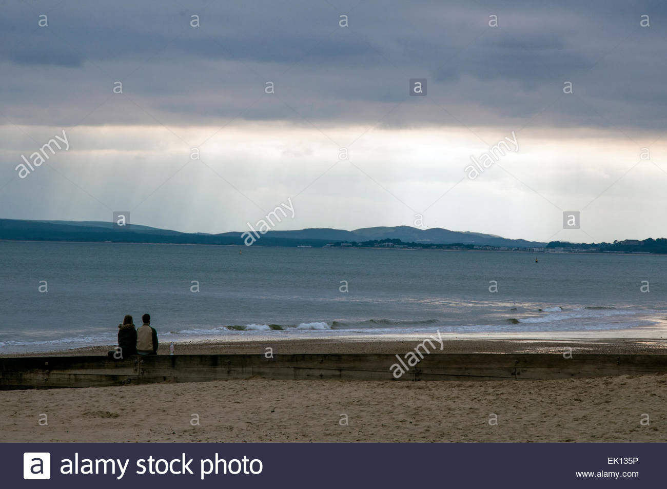Bournemouth, Dorset, England. 4th April 2015. UK weather. A young couple sits on a groyne and watches rays of sunshine - Stock Image