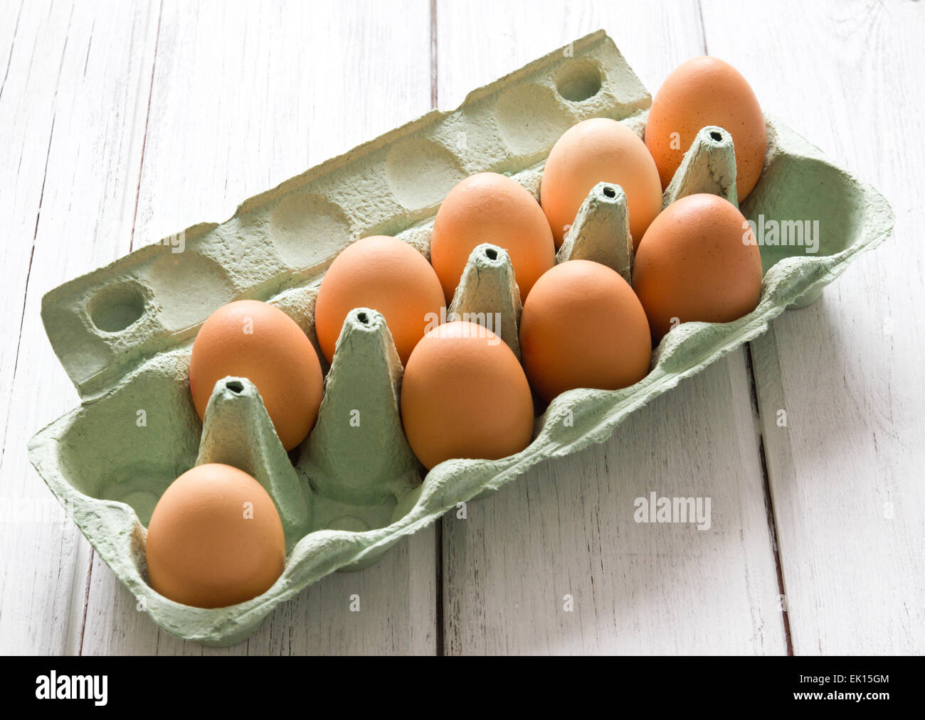 Nine fresh chicken eggs in green egg-box on white painted wooden background Stock Photo