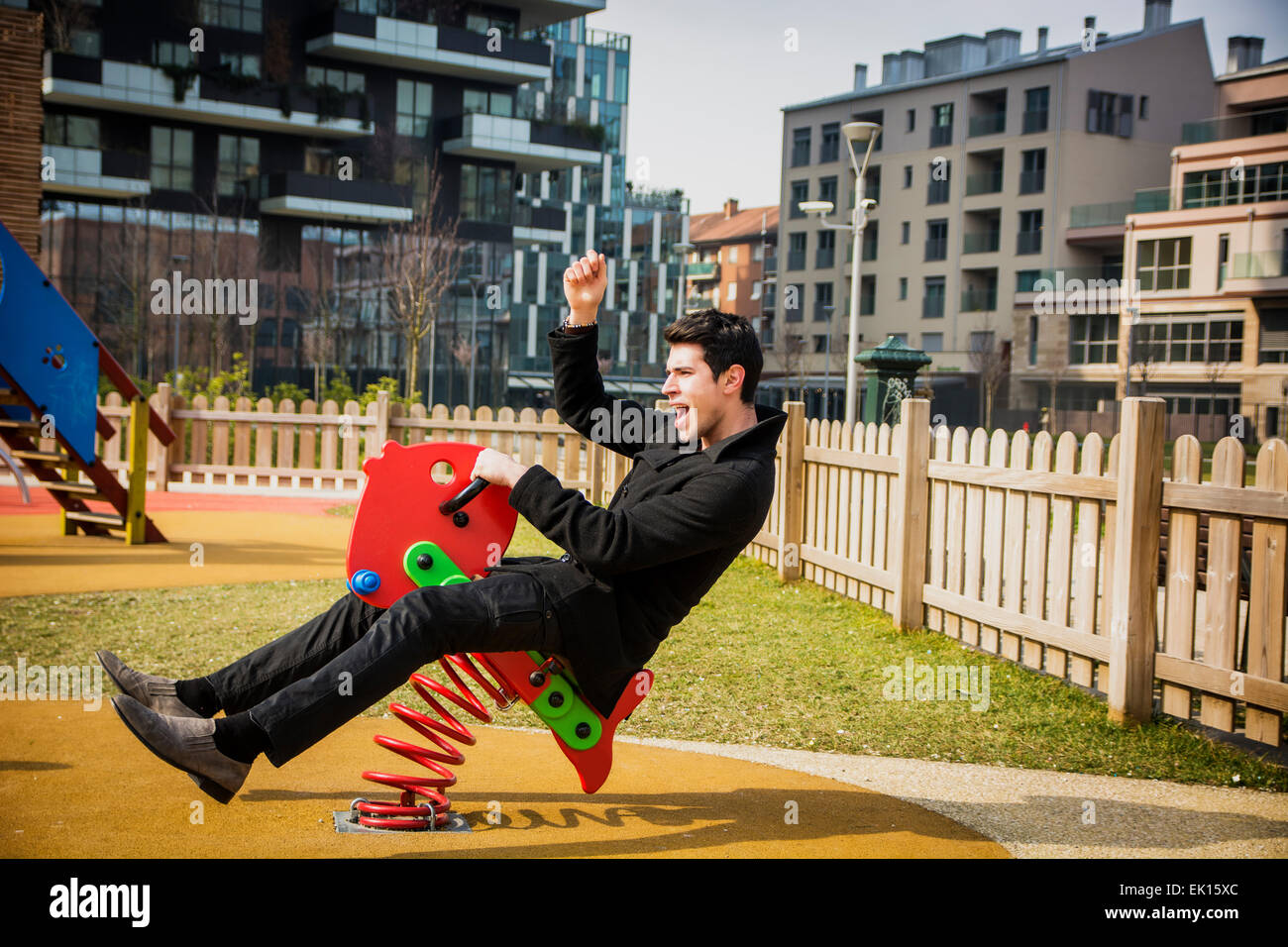 Young man reliving his childhood plying in a children's playground riding on a colorful red spring seat with - Stock Image