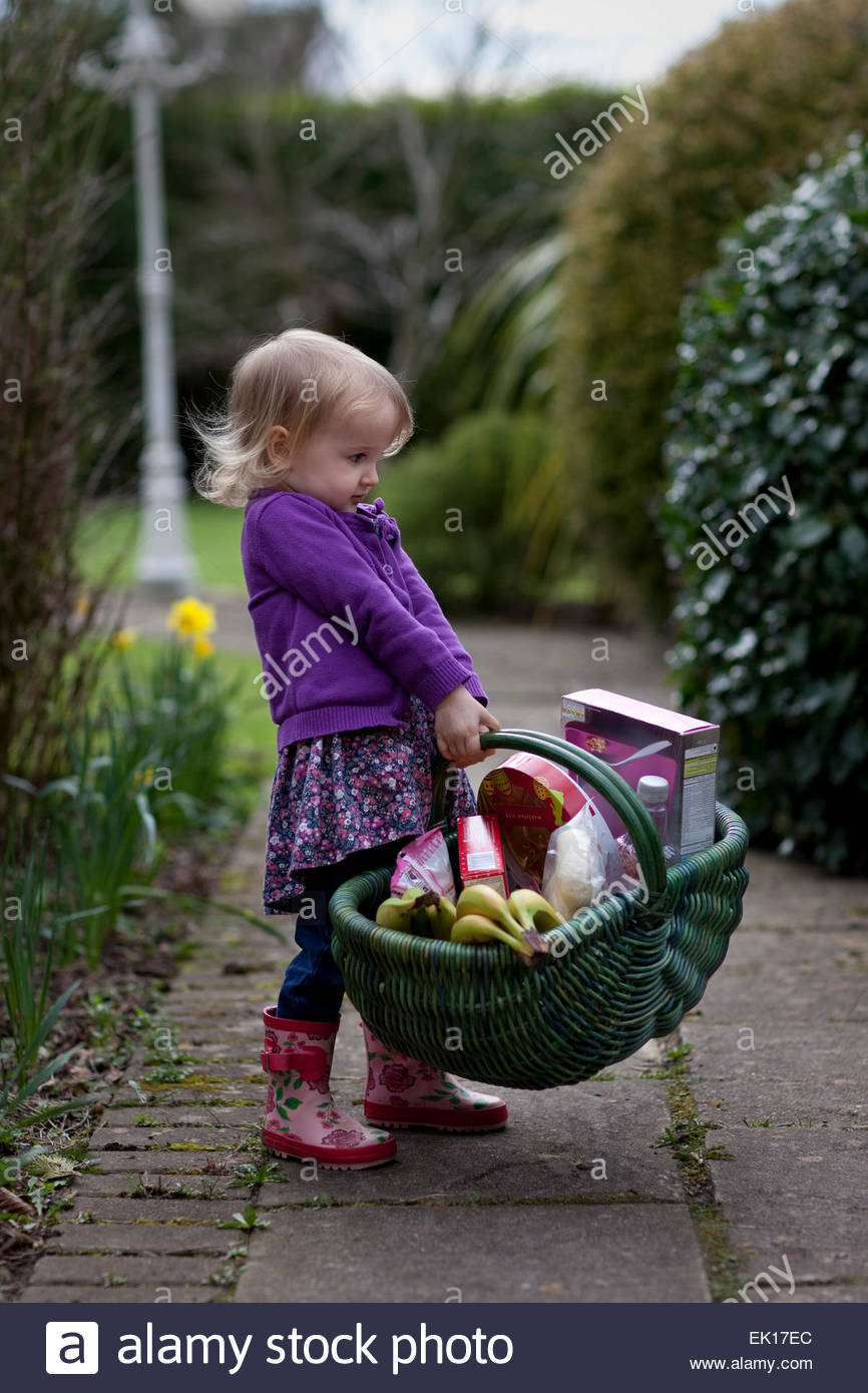 Child carrying a wicker basket full of groceries. - Stock Image