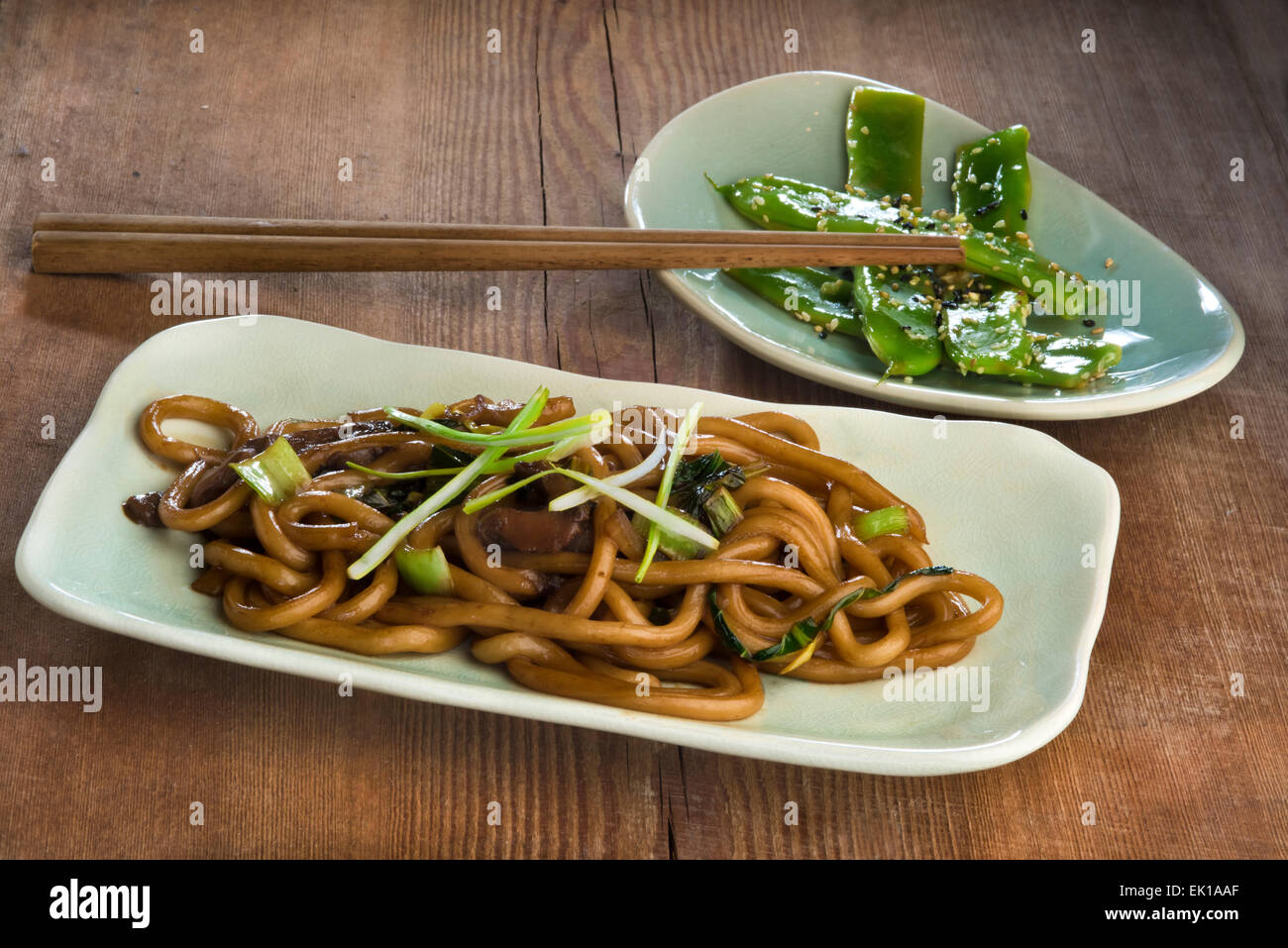 Stir fried udon noodles with bok choy, oyster mushroom and scallions and green beans fried with garlic and sesame. - Stock Image