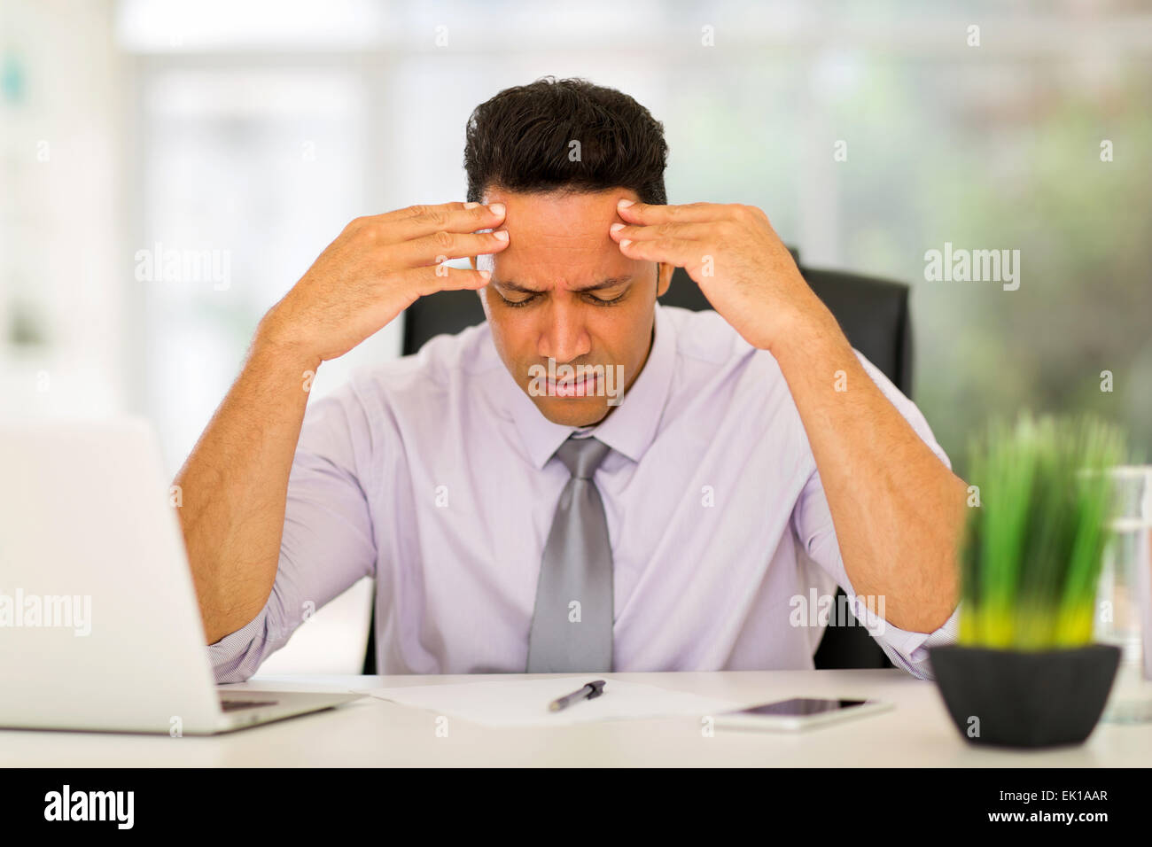 overworked businessman sitting in office - Stock Image