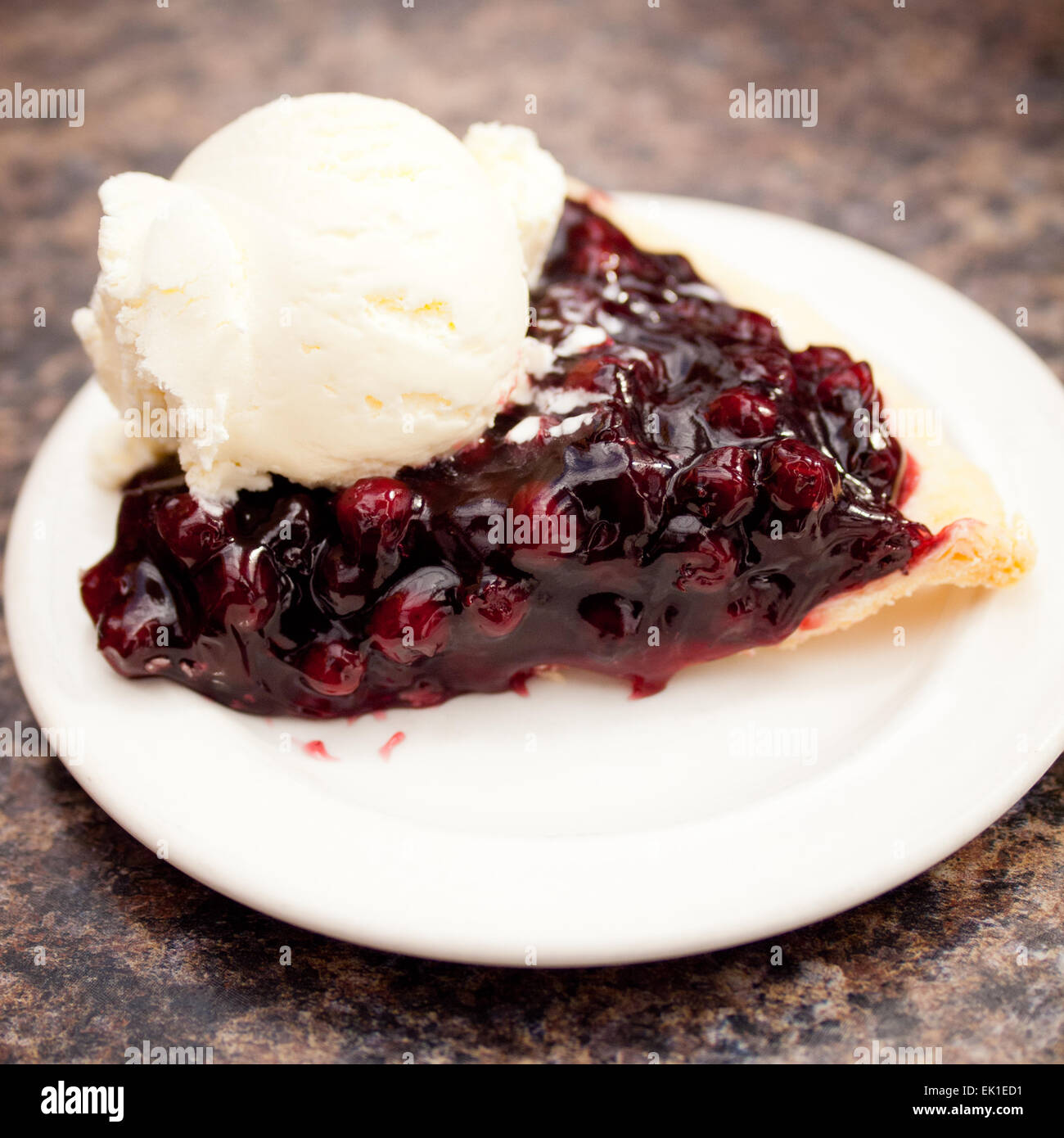 A slice of Saskatoon berry pie and a scoop of vanilla ice cream from