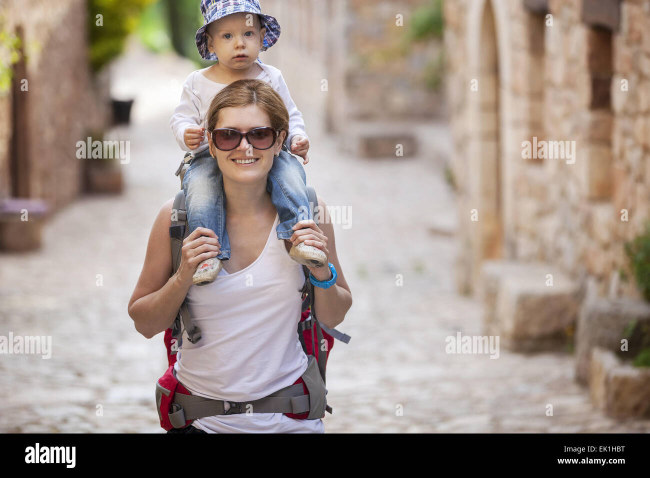 Young Caucasian woman tourist carrying her little son on shoulders - Stock Image