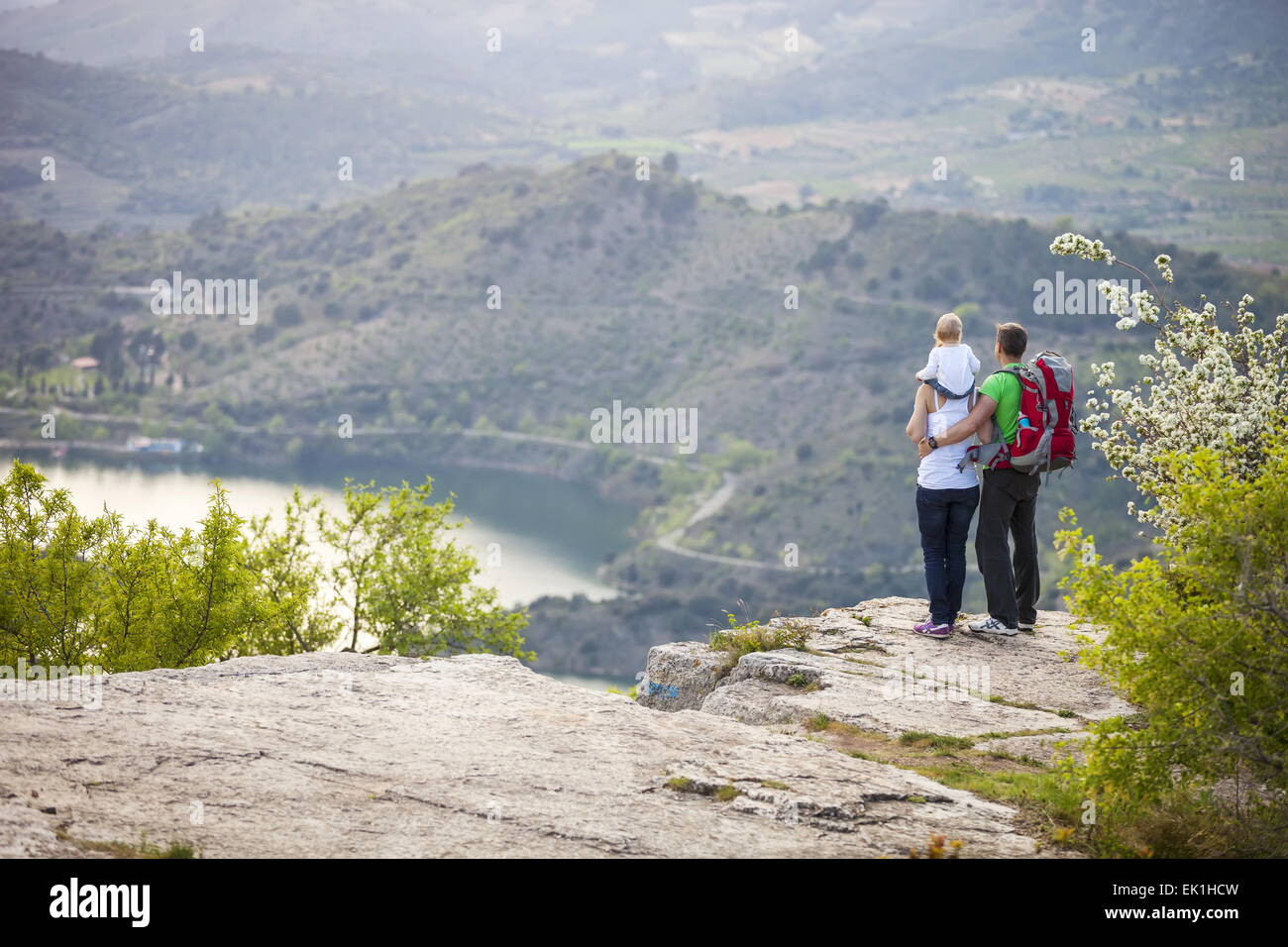 Young couple with toddler boy standing on cliff and enjoying view below - Stock Image