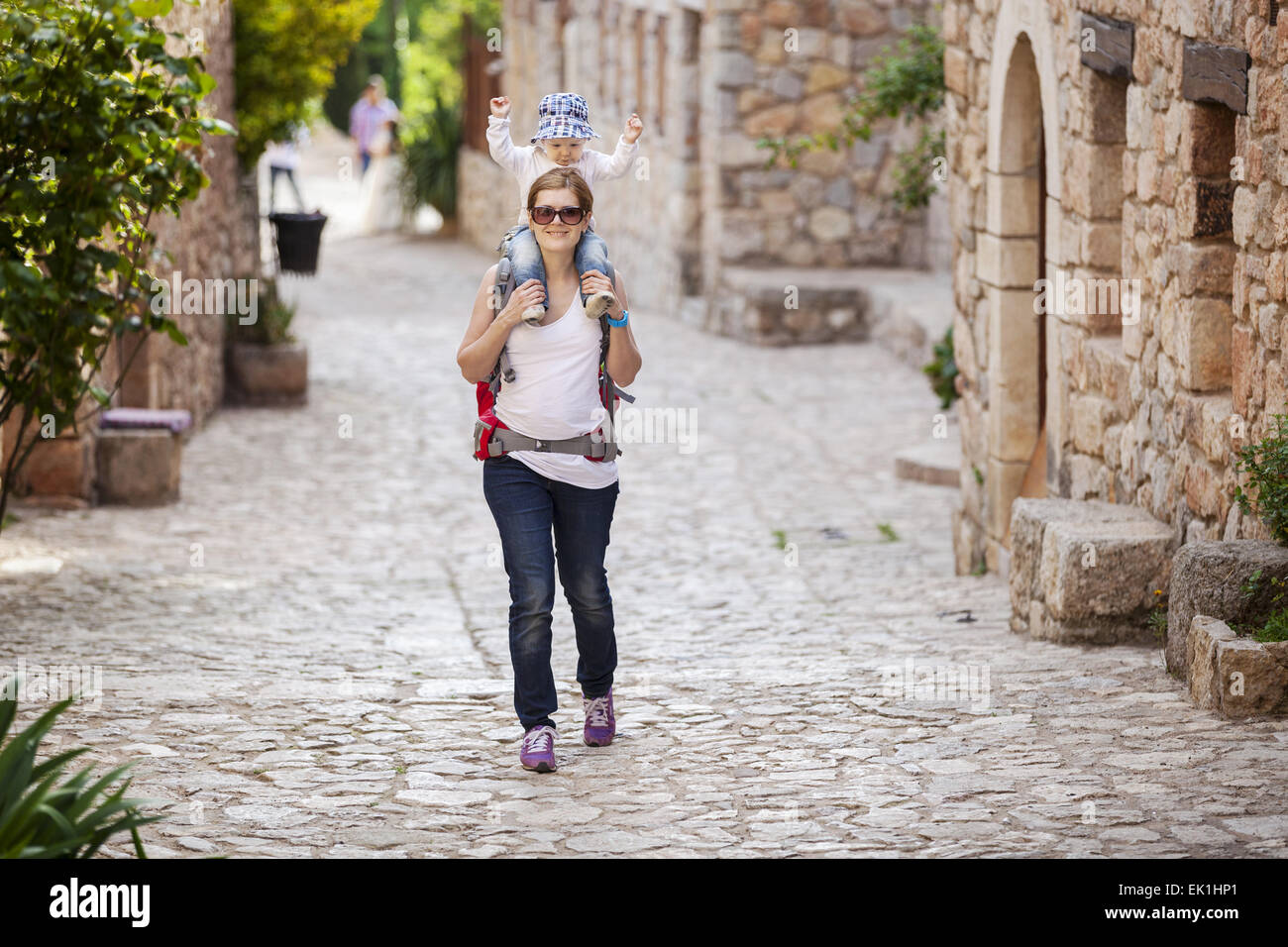 Young Caucasian woman tourist carrying her little son on shoulders while exploring old Spanish town - Stock Image