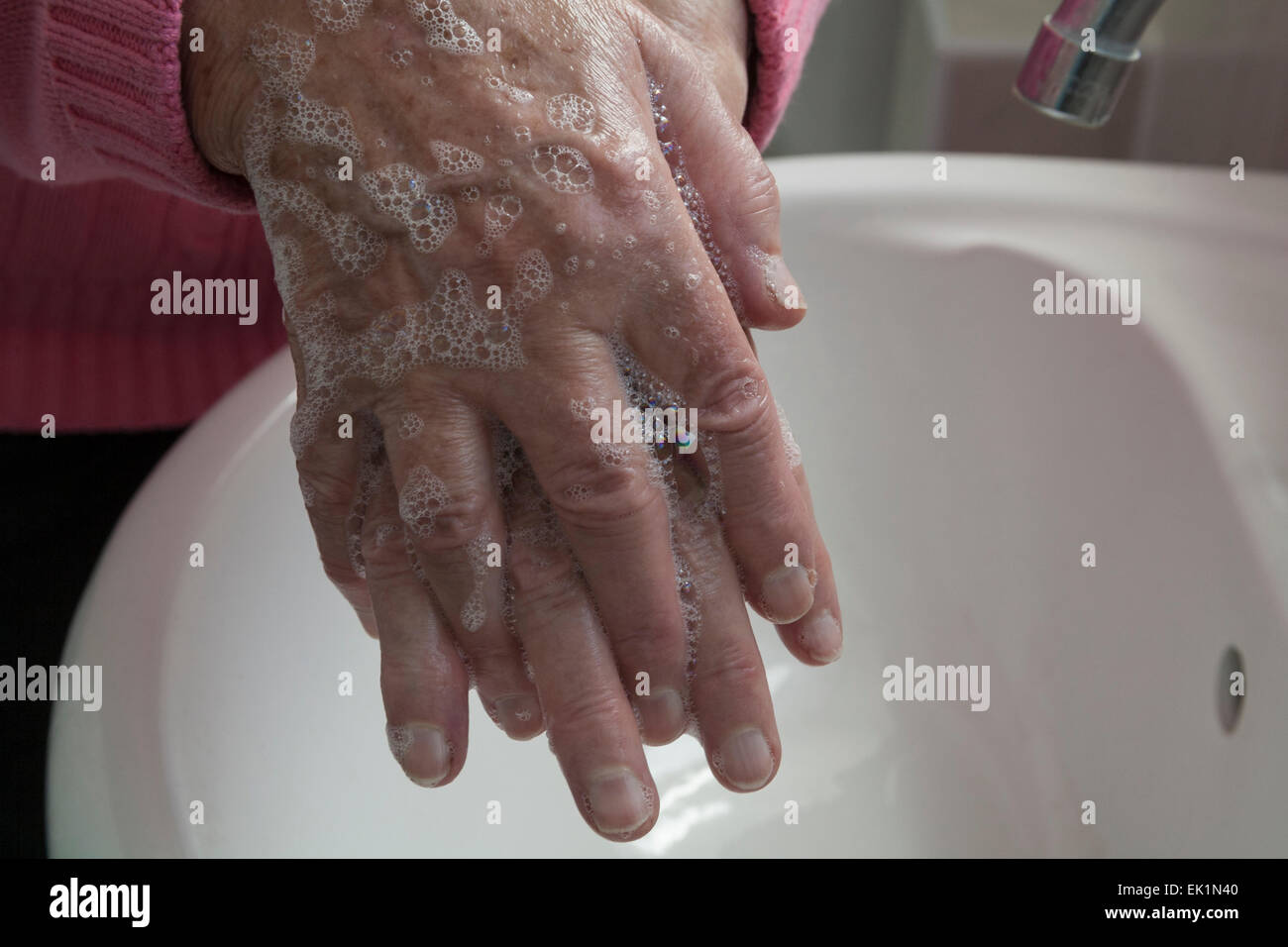 Close up Elderly woman washing hands in bathroom washbasin personal hygiene killing germs - Stock Image