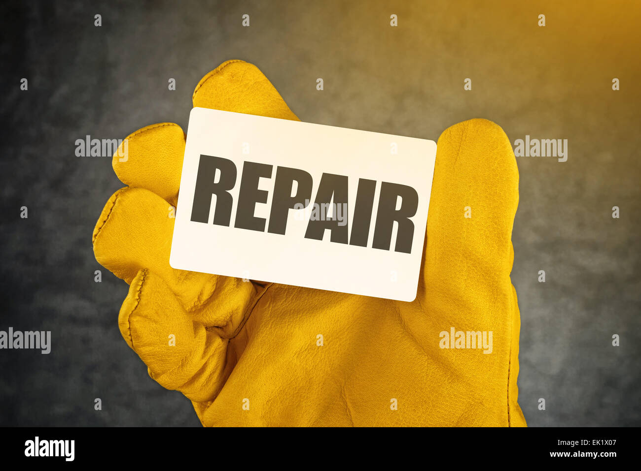 Repair on Business Card, Male Hand in Yellow Leather Construction Working Protective Gloves Holding Card with Rounded Stock Photo