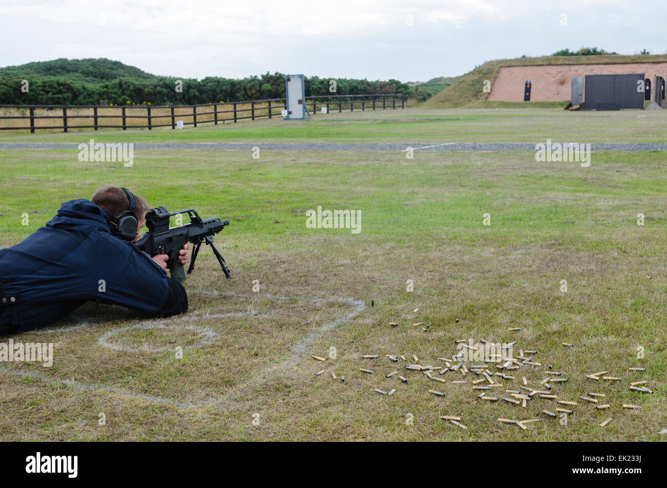 A man shoots a Remington 700 sniper rifle at a target on a firing range - Stock Image