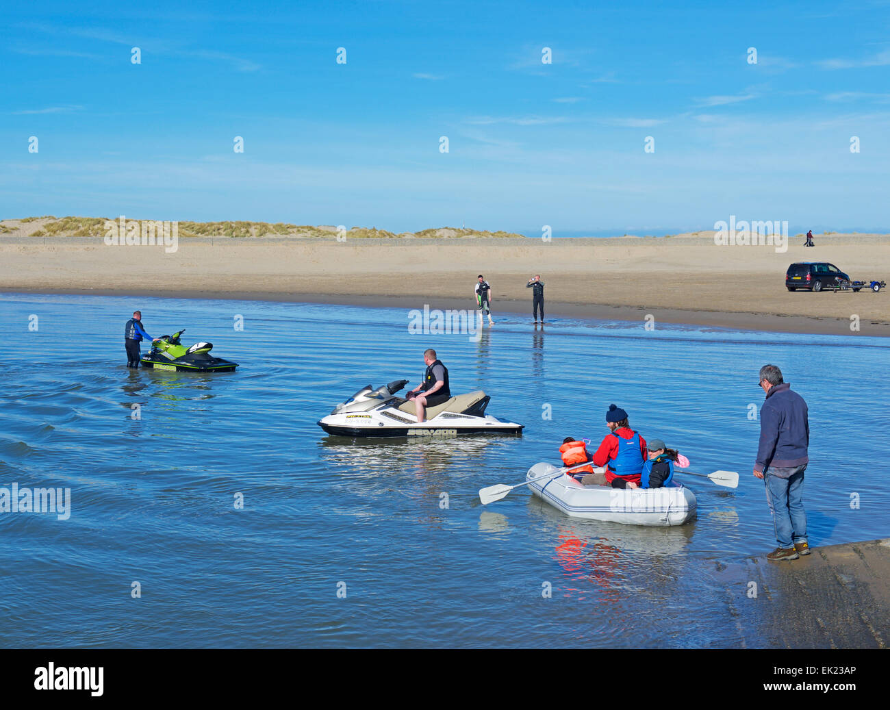 Jetskis and family in inflatable dinghy at Barmouth, Gwynedd, Wales UK - Stock Image