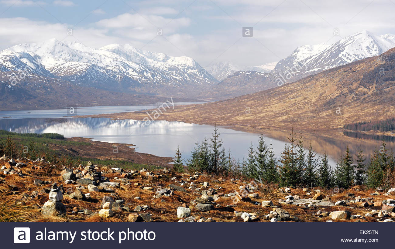 The snow capped Knoydart mountain range reflecting on Loch Loyne in the North west Scottish highlands. - Stock Image